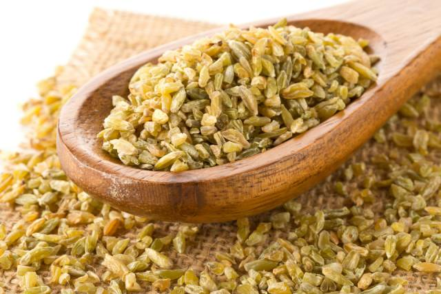 Freekeh (Roasted Wheat Grains) On a Wooden Spoon.
