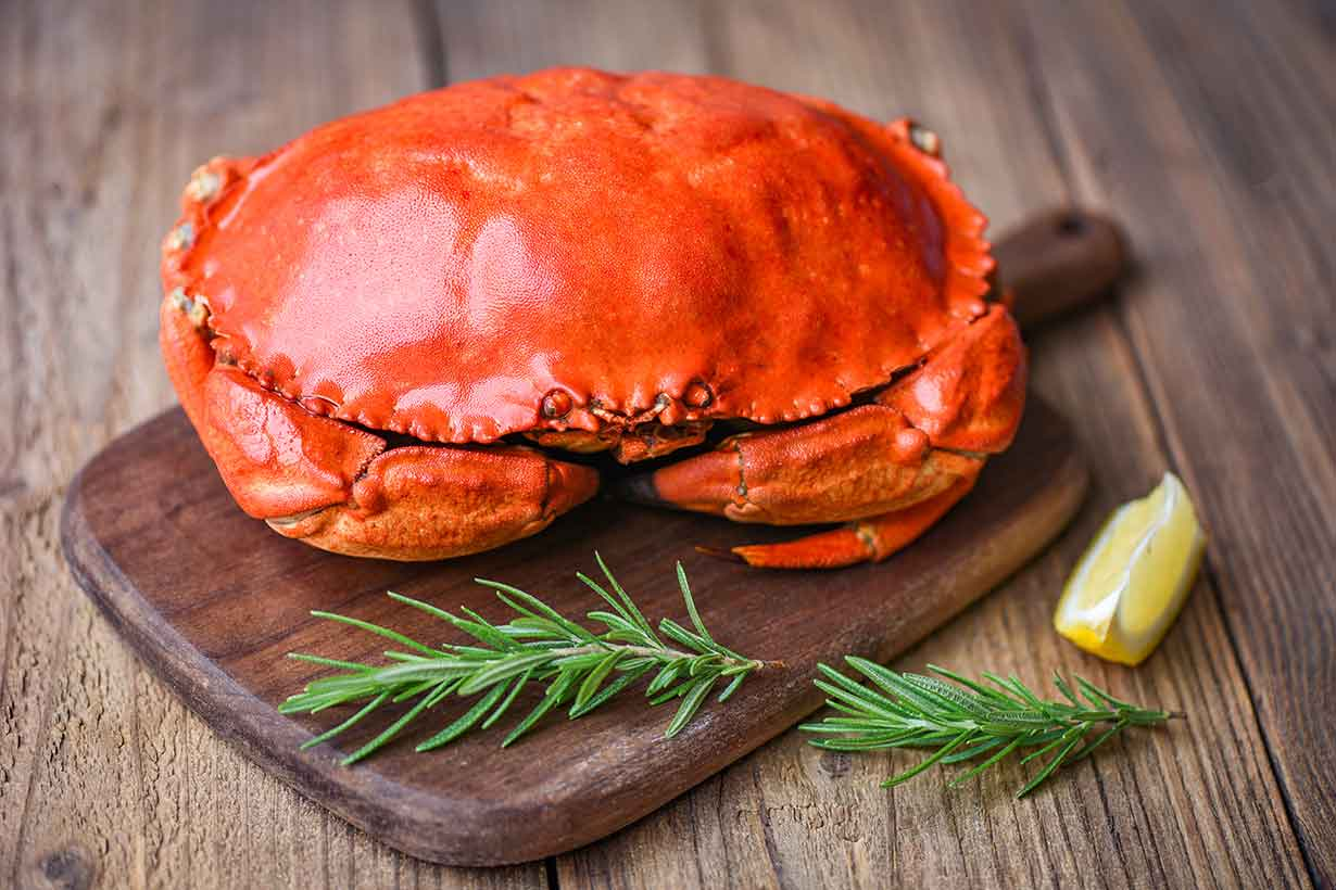 A Whole Cooked Crab On a Wooden Board.