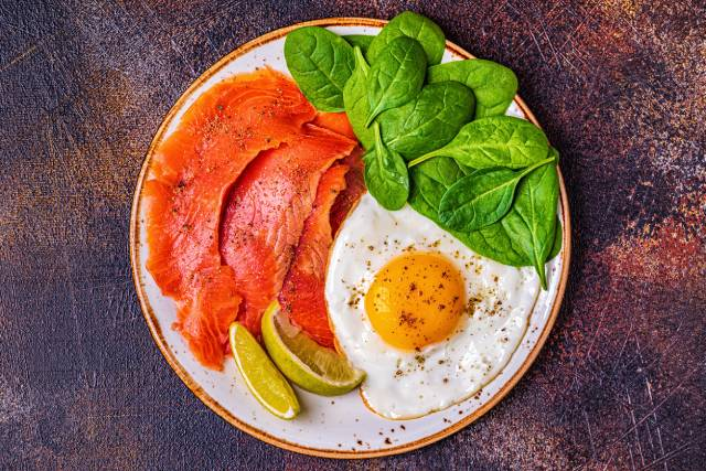 A Ketogenic Diet Meal Featuring Smoked Salmon, Fried Egg, and Leafy Greens.