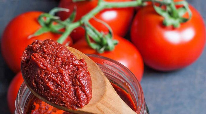 Tomato Paste On a Wooden Spoon With Whole Tomatoes in the Background.