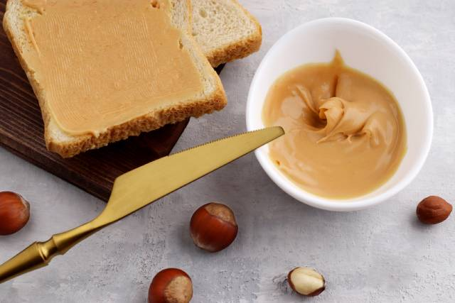 Hazelnut Butter In a White Bowl and Spread On Bread.