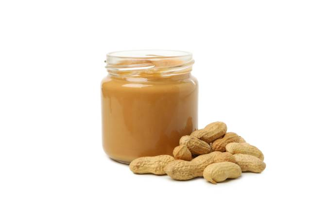 A Jar of Smooth Peanut Butter Next To Whole Peanuts.