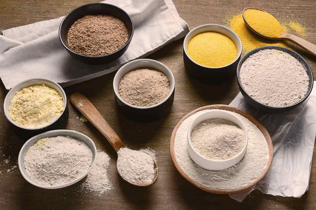 Different Types of Flour In Bowls On a Wooden Table.