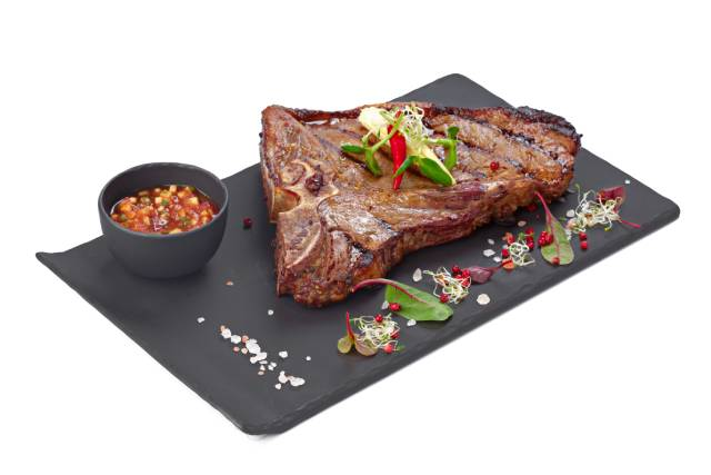 Cooked Steak On a Black Plate.
