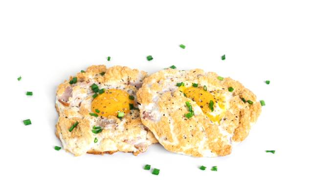 Two baked eggs with ham, cheese, and chives.