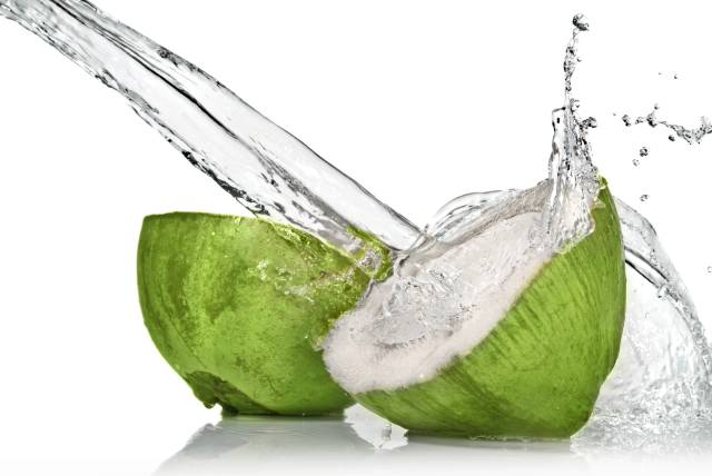 Fresh green coconut cut in half with coconut water spilling out of it.