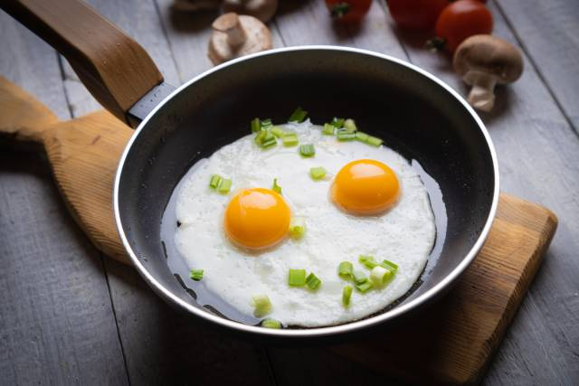 Two fried eggs in a black pan.