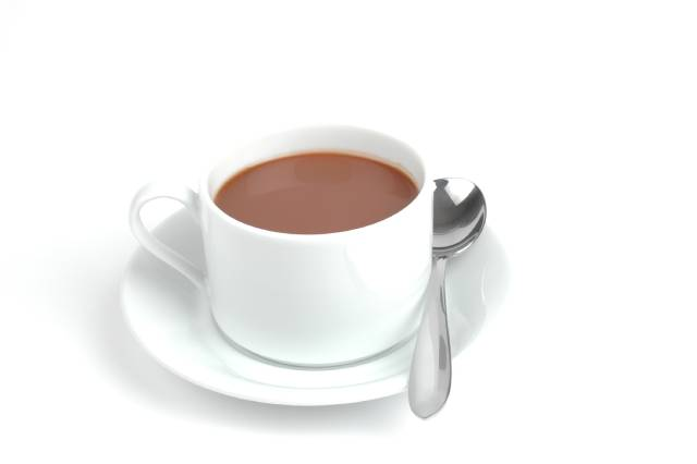 Hot chocolate in a white cup on a saucer with a teaspoon.