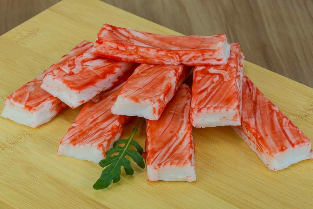 Imitation Crab Meat Sticks On a Wooden Surface.