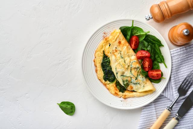 An omelet served with spinach and cherry tomatoes.