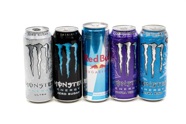 Various cans of energy drinks in a line (Red Bull, Monster).