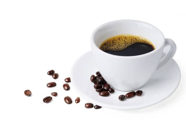 White cup full of black coffee on a white saucer.