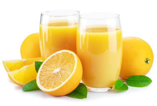Whole and Half Oranges Next To Two Glasses of Fruit Juice.
